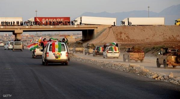 Kurds in Turkey celebrate waving the Iraqi Kurdish Regional Government's (KRG) flag as a Peshmerga fighters convoy cross through at the Habur border along the Turkish-Iraqi border with heavy weapons on October 29, 2014.  Heavily armed Kurdish peshmerga fighters were on their way by land and by air, joining militias defending the Syrian border town of Kobane, also known as Ain al-Arab, from the Islamic State group after setting off from Iraq.  Kobane's Kurdish defenders have been eagerly waiting for the peshmerga since Turkey last week said it would allow them to traverse its territory to enter the town. AFP PHOTO/ILYAS AKENGIN        (Photo credit should read ILYAS AKENGIN/AFP/Getty Images)