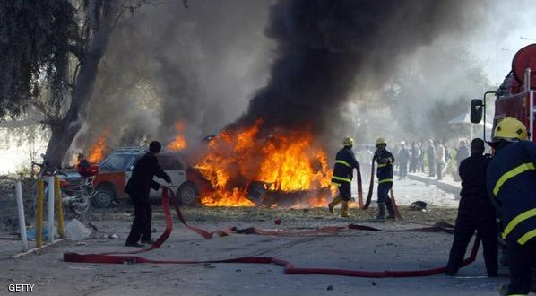 Vehicles burn as fire fighters douse the