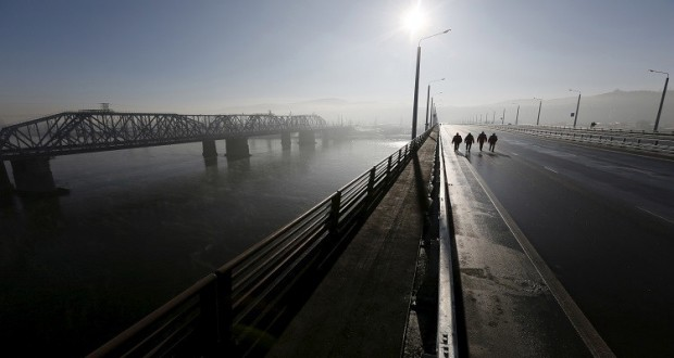 "Engineers walk along a new highway bridge before an opening ceremony, with the Yenisei River and a bridge of the Trans-Siberian Railway seen nearby, in the Siberian city of Krasnoyarsk, Russia, October 29, 2015. The construction of the 1273, 35-metre-long highway bridge, connecting the M-53 ""Baikal"" and M54 ""Yenisei"" federal highways, began in October 2011 and cost about 12 billion Russian roubles, according to local media. The Yenisei divides Siberia between Western and Eastern (back) parts while the bridge serves as a link between them. REUTERS/Ilya Naymushin - RTX1TSFG"