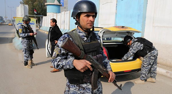 An Iraqi police officer stands guard as colleagues search a car at a checkpoint in Baghdad
