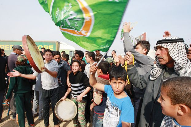 Displaced Iraqi people, who fled the violence in the Iraqi city of Ramadi, celebrate after their city was liberated from the Islamic State group on December 29, 2015 at the Alkzenzanah camp in the capital Baghdad. Iraqi Prime Minister Haider al-Abadi congratulated the fighters who retook Ramadi, vowing to liberate the second city of Mosul and rid the entire country of IS in 2016.    AFP PHOTO / SABAH ARAR