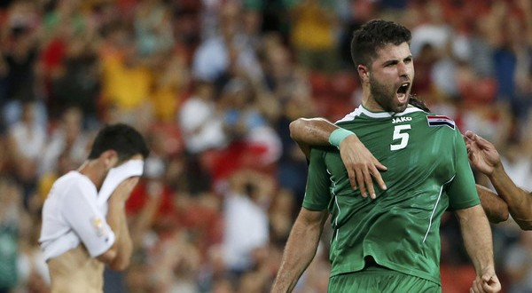 Iraq's Yaser Safa Kasim (R) celebrates his goal as Jordan's Yousef Ahmad Mohammad (L) reacts during their Asian Cup Group D soccer match at the Brisbane Stadium in Brisbane January 12, 2015. REUTERS/Edgar Su (AUSTRALIA  - Tags: SOCCER SPORT TPX IMAGES OF THE DAY)