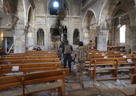 جنود من القوات العراقية الخاصة داخل كنيسة دمرها مقاتلو تنظيم الدولة الاسلامية في برطلة شرق الموصل بالعراق يوم الجمعة. تصوير: جوران توماسيفيتش - رويترز.